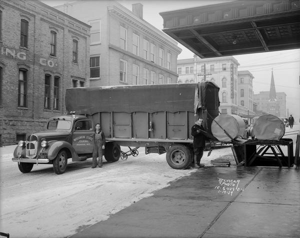 Large rolls of newsprint paper being unloaded in from of the Wisconsin State Journal building at 115 S. Carroll Street, circa 1939