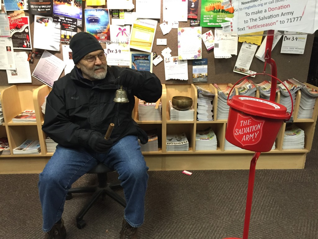 Rick, a Salvation Army volunteer, rings a bell from Nepal as he collects donations in a traditional Red Kettle at Metcalfe's Market. His untraditional singing bowl bell rests on the magazines stacked behind him.